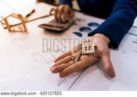 Realtor Real Estate Or Home Seller Showing Key House And Calculatate Price Of Housing. Offer Of Purc