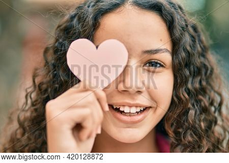 Hispanic teenager girl smiling happy holding heart over eye at the city.