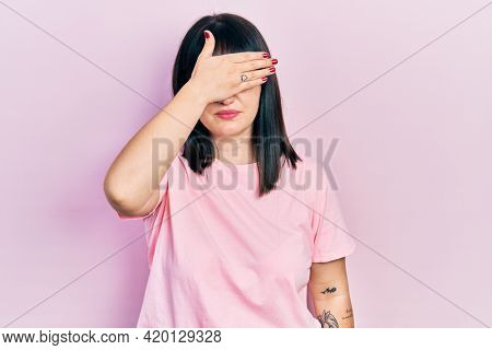 Young hispanic woman wearing casual clothes covering eyes with hand, looking serious and sad. sightless, hiding and rejection concept