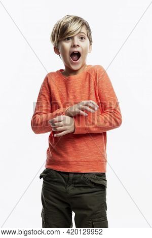A 9-year-old Boy In An Orange Sweater And Jeans Shouts In Fright. White Background. Vertical.