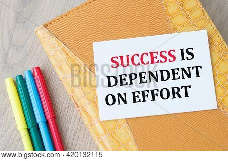 Card With Text Success Is Dependent On Effort Sheet On A Notebook That Lies On The Table. Business C