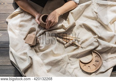 Woman Sitting By Table, Kneading Clay And Making Earthenware At Lesson