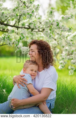 Mother Sit, Holds Young Son In Flowering Spring Garden. Parental Love And Care