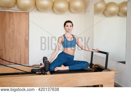 An Athletic Woman Does Exercises On A Reformer While Doing Pilates.