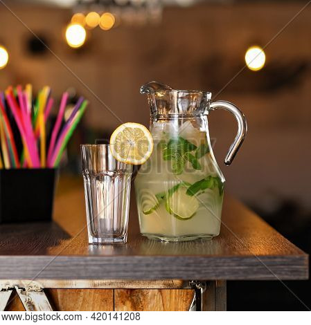 Glassware With Refreshing Drink At Wooden Table. Citrus Tropical Cocktail Or Lemonade Drink On Backl