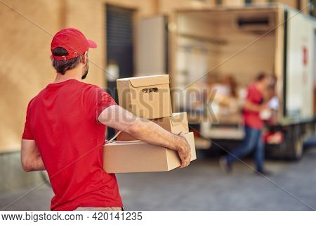 Rear View Of A Male Courier In Red Uniform Holding Parcels For Delivery While Standing At Storehouse