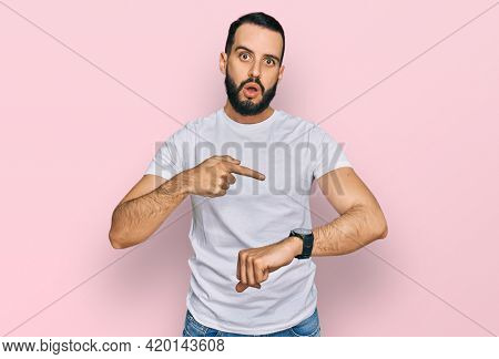 Young man with beard wearing casual white t shirt in hurry pointing to watch time, impatience, upset and angry for deadline delay