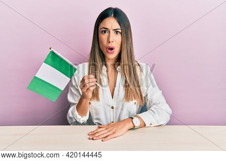 Young hispanic woman holding nigeria flag sitting on the table scared and amazed with open mouth for surprise, disbelief face