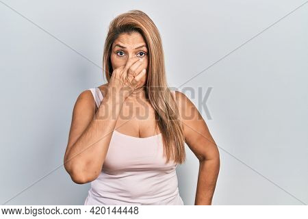 Middle age hispanic woman wearing casual style with sleeveless shirt smelling something stinky and disgusting, intolerable smell, holding breath with fingers on nose. bad smell