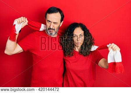 Middle age couple of hispanic woman and man wearing scarf team football hooligan cheering game skeptic and nervous, frowning upset because of problem. negative person.