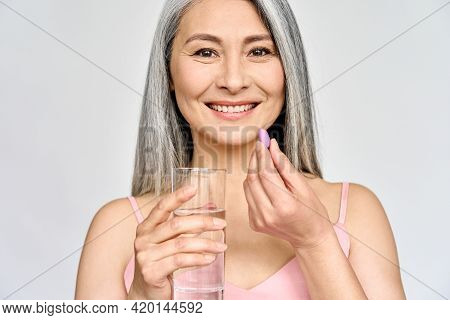 Happy Middle Aged 50s Asian Woman Holding Pill And Glass Of Water Taking Dietary Supplements. Portra