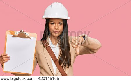 Beautiful hispanic woman architect showing black space on clipboard with angry face, negative sign showing dislike with thumbs down, rejection concept