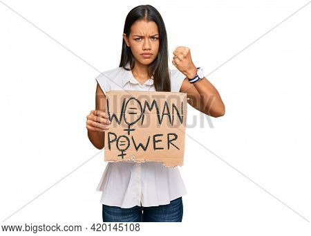 Beautiful hispanic woman holding woman power banner annoyed and frustrated shouting with anger, yelling crazy with anger and hand raised