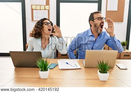 Middle age hispanic woman and man sitting with laptop at the office shouting and screaming loud to side with hand on mouth. communication concept.