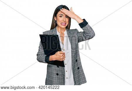 Young hispanic woman wearing business clothes holding clipboard stressed and frustrated with hand on head, surprised and angry face
