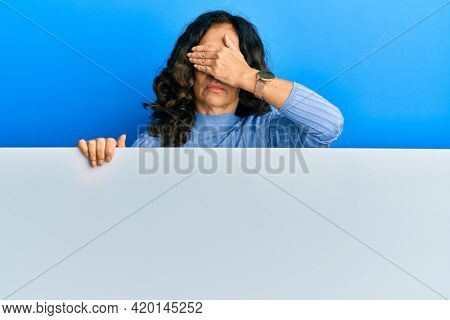 Middle age hispanic woman holding blank empty banner covering eyes with hand, looking serious and sad. sightless, hiding and rejection concept