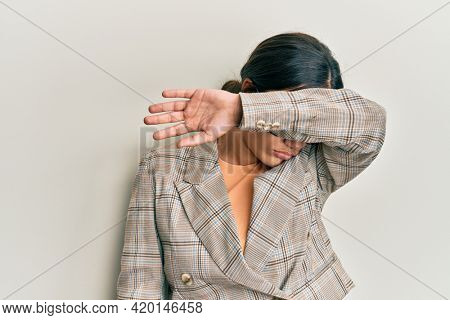 Young brunette woman wearing business jacket and glasses covering eyes with arm, looking serious and sad. sightless, hiding and rejection concept