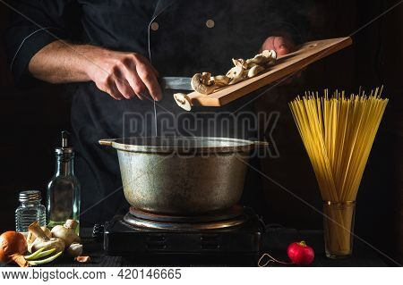 The Chef Prepares Soup On The Background Of Vegetables And Spaghetti. Close-up Of A Cook Hand Pourin