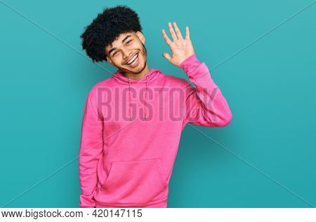 Young african american man with afro hair wearing casual pink sweatshirt waiving saying hello happy and smiling, friendly welcome gesture