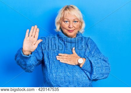 Middle age blonde woman wearing casual clothes swearing with hand on chest and open palm, making a loyalty promise oath