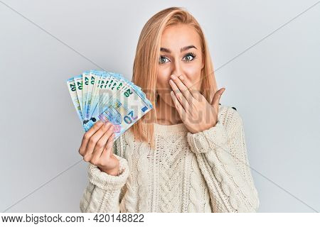 Beautiful caucasian blonde woman holding 20 euro banknotes covering mouth with hand, shocked and afraid for mistake. surprised expression