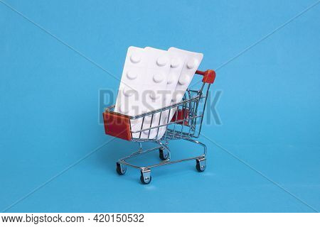 Pills In A Shopping Basket On A Blue Background