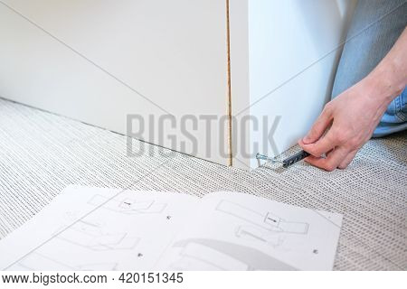 Left Hand Tightening A Corner With A Screw On White Furniture On Floor At Home, Using Assembly Manua