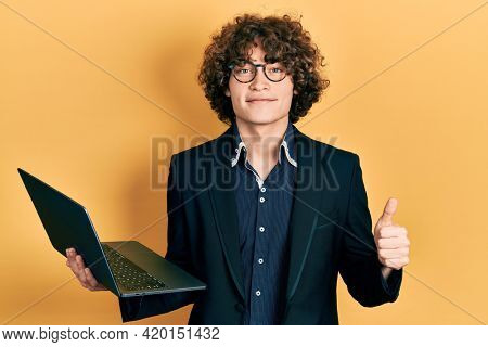 Handsome young man working using computer laptop smiling happy and positive, thumb up doing excellent and approval sign