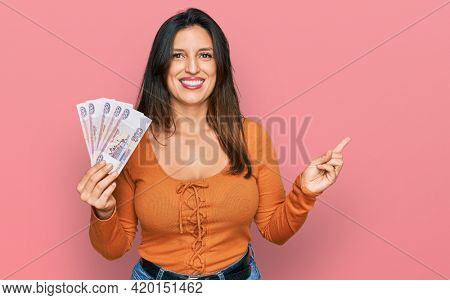 Beautiful hispanic woman holding russian 500 ruble banknotes smiling happy pointing with hand and finger to the side