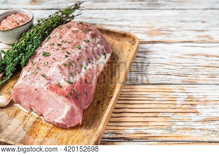 Raw Whole Boneless Pork Loin Meat With Thyme And Salt On Rustic Board. White Wooden Background. Top