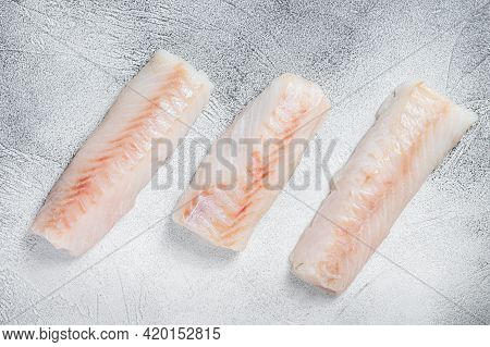 Raw Norwegian Cod Fish Fillet On Kitchen Table. White Background. Top View