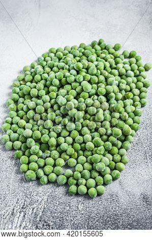 Raw Frozen Green Peas On Kitchen Table. White Background. Top View