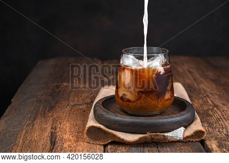 Iced Coffee With Milk, Cold Drink In A Glass On A Dark Background. Pouring Milk Into Coffee. Copy Sp