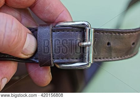 A Brown Leather Harness With A Gray Metal Fastener Lies On The Fingers On A Green Background