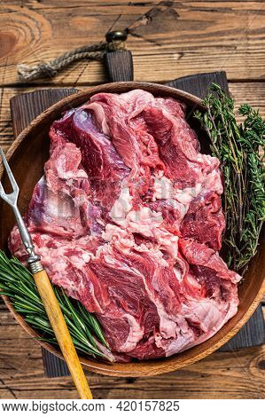 Boneless Raw Mutton Lamb Shoulder Meat In Wooden Plate With Herbs. Wooden Background. Top View
