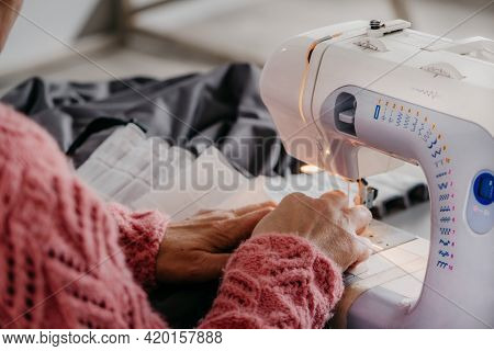 Close-up. The Hands Of An Adult Woman Are Sewing At A Sewing Machine. Manufacture Of Wearing Apparel