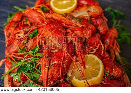 Boiled Crayfish On A Black Background With Herbs And Lemon Juice. Boiled Delicious Crayfish