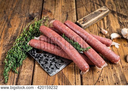 Uncooked Raw Beef And Pork Sausage On Vintage Meat Cleaver. Wooden Background. Top View