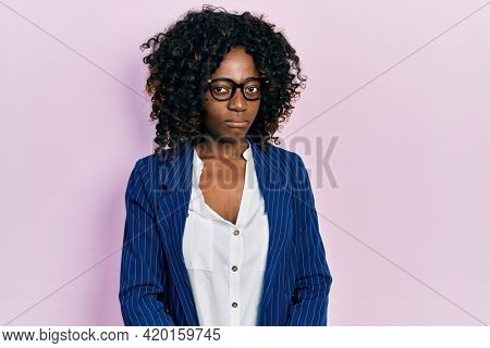 Young african american woman wearing business clothes and glasses skeptic and nervous, frowning upset because of problem. negative person.