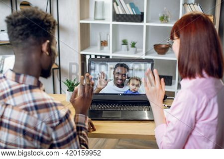 Young Multicultural Couple Having Video Call On Modern Laptop With African Man That Holding Cute Bab