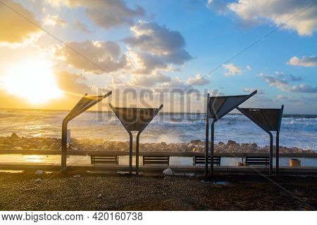 Powerful winter surf takes off with snow-white foam. Embankment in Tel Aviv. Sunset. Windy sunny day on the Mediterranean coast. Winter storm in the Mediterranean. Israel.