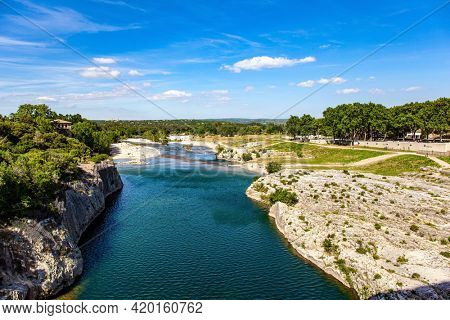 Interesting trip to France. The shallow Gardon River in a bright sunny day. Antique bridge - aqueduct  - the Pont du Gard