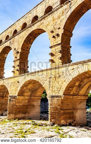 The Pont du Gard is the tallest Roman aqueduct. Picturesque antique aqueduct. The shallow Gardon River in a bright sunny day. Interesting trip to France.