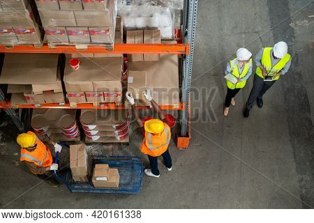 Directly above view of stockroom workers in reflective vests and hardhats working with each other while distributing goods