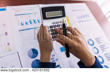 Accountant Woman Using A Calculator With A Pen In Her Hand To Calculate Expenses, Accounting, Financ