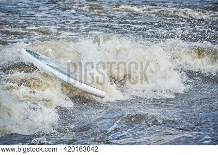 stand up paddleboard with a paddler under water after running rapids in the Poudre River Whitewater Park.