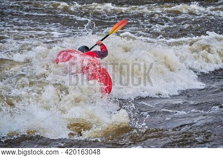 kayaker is surfing a wave in the Poudre River Whitewater Park in downtown of Fort Collins, Colorado