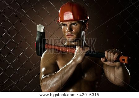poster of the beauty muscular worker chopper man with big heavy ax in hands tired appearance on netting fence background