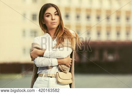 Happy young fashion woman walking on city street Stylish female model with pullover in white shirt and jeans