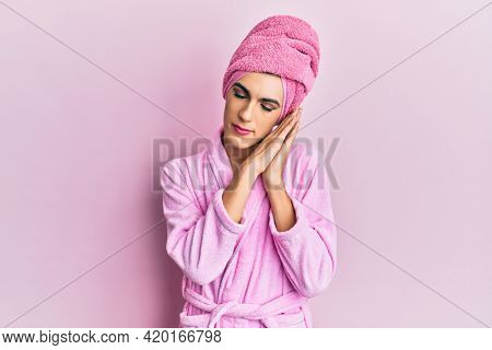 Young man wearing woman make up wearing shower towel on head and bathrobe sleeping tired dreaming and posing with hands together while smiling with closed eyes.